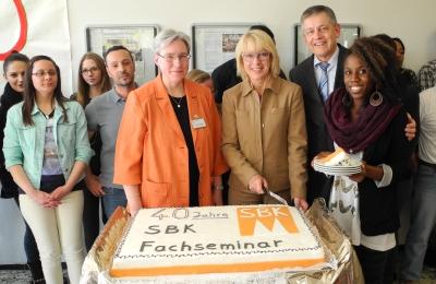 Bürgermeisterin Elfi Scho-Antwerpes schneidet die Geburtstagstorte an – daneben Mechthild Kutscher, Leiterin des Fachseminars und Otto B. Ludorff, SBK-Geschäftsführer sowie Schülerinnen und Schüler des SBK-Fachseminars für Altenpflege.